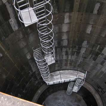 Cage ladder with rest platforms used in an industrial reservoir / well.