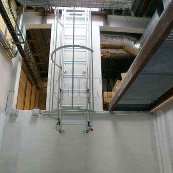 Drop-down ladder with a cage in an industrial environment.