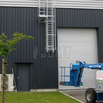 Drop-down ladder with double cage and resting platform outside of a warehouse.
