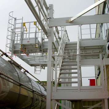 Platform accessed by stairs and equipped with cage ladders for accessing tanker truck manholes.