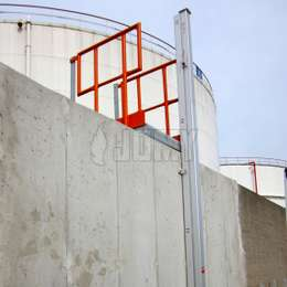Closed JOMY retractable ladder installed on a facility wall outside of a storage tank area.