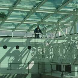 Telescopic gantry on mobile deck for glass roof cleaning.