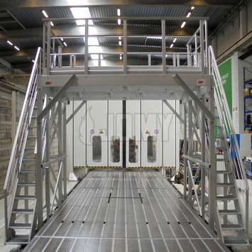 Industrial work platform with access stairs and removable trap on a motor factory production line.