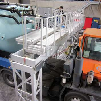 Workplatform for tanker trucks with a levee-bridge system.